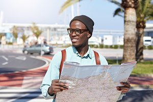 Outdoor shot of carefree and relaxed young dark-skinned student dressed in trendy clothing holding paper map in urban setting while sightseeing alone, looking for new beautiful places and adventures