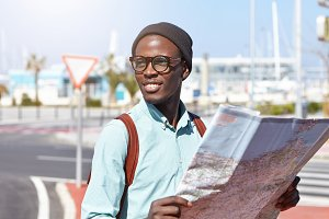 Here it is. Joyful African American backpacker holding paper map in his hands while sightseeing in resort town, searching for tourist destinations and landmarks, having interested and cheerful look