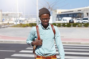 Stylish young dark-skinned male tourist in headwear and hipster glasses adjusting strap of his leather backpack while crossing street in foreign city, deep in thoughts, enjoying summer vacations