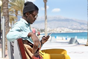 Sideview outdoor portrait of cheerful stylish young Afro American man sitting on bench along promenade at seaside, using free city wi-fi while chatting with friends via social networks on cell phone