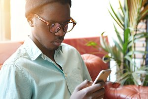 Portrait of concentrated young black businessman on vacations sitting on leather couch at hotel lobby, using mobile phone, checking e-mail and waiting for morning coffee, dressed in stylish clothes