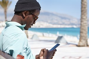 Attractive fashionable black European guy relaxing at daytime, sitting on bench by the sea, holding and using modern electronic device for networking, enjoying online communication with friends
