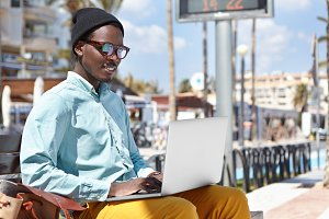 Attractive cheerful young African American male freelancer dressed in stylish wear sitting on urban bench with laptop computer on his lap and using free wireless internet connection for remote work