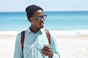Young African American hipster typing text messages on smart phone while relaxing at seaside at daytime. Stylish black male using electronic gadget on beach, blue ocean and white sand in horizon