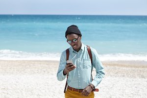 Outdoor shot of Afro American young man with backpack wearing hat, shades and stylish clothes waiting for his date on pebble beach, using 3g or 4g internet connection on touchscreen mobile phone