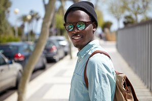 Urban summer portrait of handsome trendy looking young African American man in eyewear and hat walking on streets of foreign city, sightseeing, visiting landmarks while spending holidays abroad
