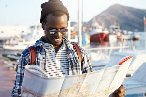 Trendy looking African American tourist with backpack in hat and sunglasses studying directions using city guide while exploring sights and landmarks of resort town, yacht parking in background