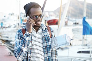 Close up outdoor portrait of charismatic young African American man in stylish clothes carrying paper map under his arm, having nice phone conversation, standing on background of harbor and yachts