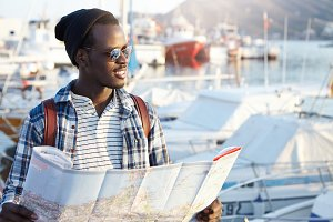 Outdoor portrait of African man looking happy before journey, waiting for his friends in harbor, holding paper map, feeling excited and joyful, anticipating adventures, places and good experience