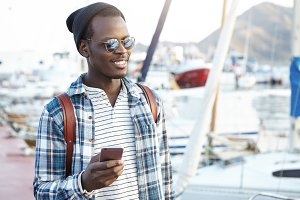 Travel, tourism, communication, technology and people concept. Handsome black man with backpack wearing stylish hat and shades texting messages on smart phone, enjoying nice sunny weather outdoors