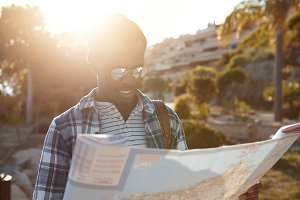 Headshot of cheerful black European guy with backpack traveling alone on foot exploring new beautiful places, holding paper map while looking for old temple in woods. People, travel and adventure