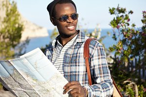 Happy carefree young African American male backpacker in mirrored lens shades and headwear planning next stop during road trip, reading paper map in his hands, standing in beautiful landscape