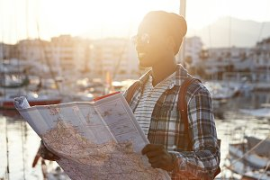 People, modern lifestyle, travel and adventure concept. Handsome African male tourist dressed in stylish wear planning route, holding big paper map in his hands before going to journey with friends