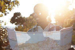 Summer portrait of attractive joyful Afro American traveler reading paper map before road trip, anticipating beautiful views, feeling excited about new interesting places and adventures. Flare sun
