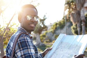 Outdoor summer portrait of handsome happy Afro American tourist wearing stylish round sunglasses and hat studying paper map in his hands, planning route during road trip. People and travel concept