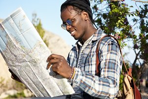 Active lifestyle, travel and tourism. Cheerful fashionable young dark-skinned traveler with backpack holding map feeling excited about road trip in mountain area standing in nature surroundings