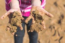 Hands of child full of wet sand on t