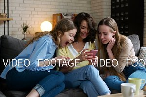 three young and energetic best friend girls look over photos in telephone mobile