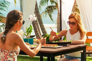 Two attractive girls have a dinner at the beach in resort