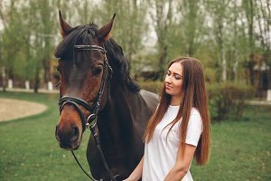 Beautiful girl communicates with a horse in the park