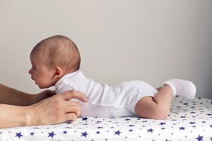 father supports his son a newborn who lies on his stomach