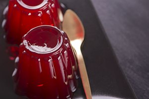 Strawberry jelly and spoon on black plate. Horizontal shoot.