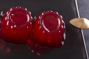 Strawberry jelly and spoon on black plate.