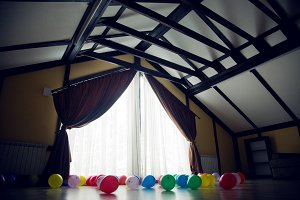 Large room with a large window and curtains with inflatable colored balls