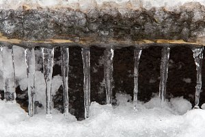 Icicles hanging from a wooden