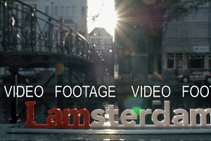I amsterdam slogan and city view with canal