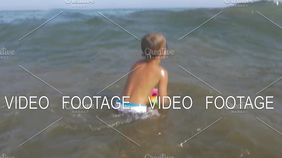 Playful Child Bathing In Sea With Ball