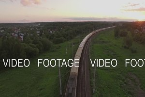 Cargo train crossing countryside at sunset, Russia