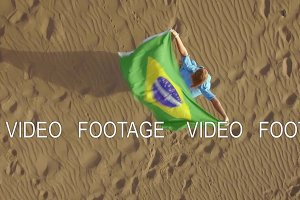Woman on the sand with Brazilian flag, aerial shot