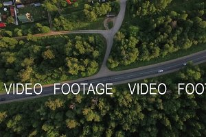 Flying over green forest and village near the road, Russia