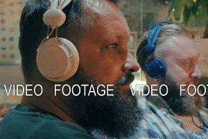 Bearded men in headphones enjoying music