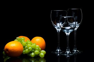 Glasses for wine, grapes and oranges on a black background