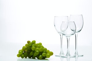 Wine glasses and a bunch of grapes on a white background