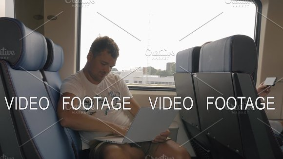 View Of Young Man Sitting In The Train And Using Laptop Against Window During Trip Netherlands