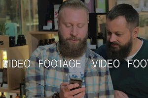Two bearded men using smart phone