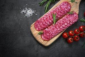 Traditional salami sliced on cutting board.