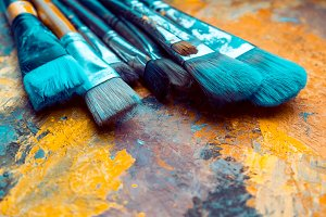 Paint brushes on artist canvas