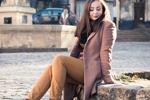 pretty girl sits on a rock
