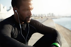 Cropped shot of African American athlete wearing black sportswear sitting outside at the sea, listening to music with earphones with thoughtful and dreamy expression while resting after jogging