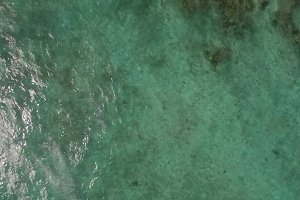 Aerial view of ocean blue water with waves, corals and water plants, Mauritius Island