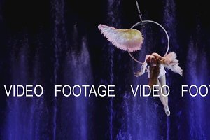 Close up view of aerial performer making acrobatic act against colorful fountains, acrobatics, Moscow, Russia
