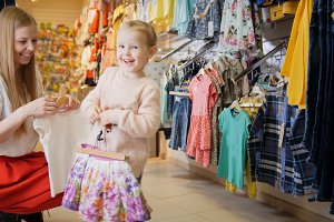 Young mother with blonde daughter buying kids clothes in store