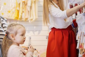 Daughter with mother buying kids clothes in store
