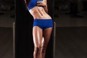 Fitness girl with perfect abdominal muscles relaxing in the gym.