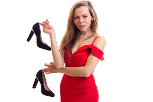 Young woman in red dress holding shoes