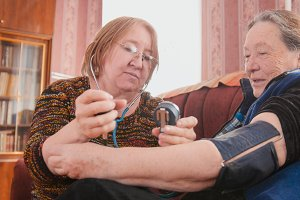 Two pensioners - checking health state with manometer - measures pressure, pensioners healthcare